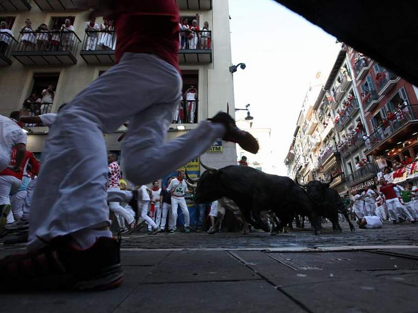 Menschen laufen beim berühmt-berüchtigten Stiertreiben im nordspanischen Pamplona vor Stieren davon. Bei dem umstrittenen Spektakel, zu dem Schaulustige aus aller Welt anreisen, werden jedes Jahr Dutzende Teilnehmer verletzt. Foto: David Domench/Europa Press