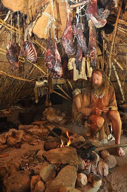 Steinzeitjäger Werner Pfeifer in einer Hütte neben einem offenen Feuer, über dem Fleisch im Rauch hängt.