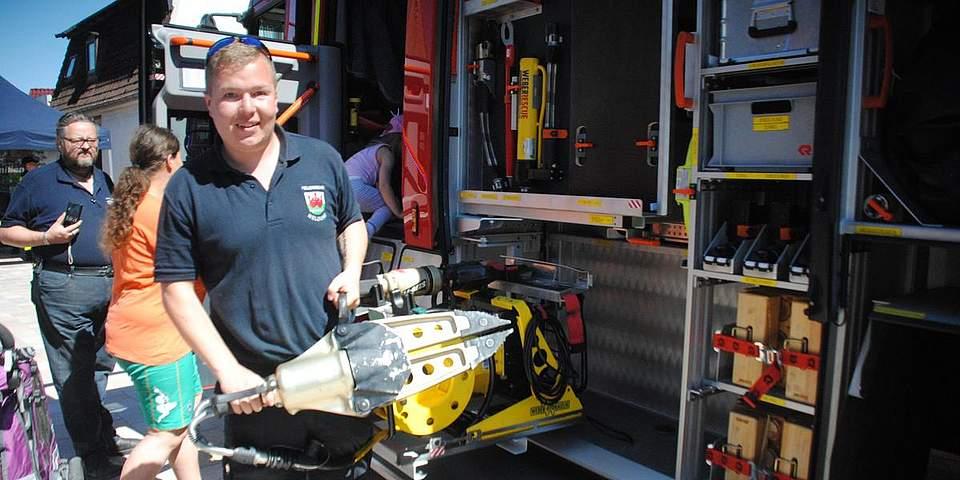 Feuerwehrmann Kevin Reimers zeigt einen Spreitzer, mit dem eingeklemmte Personen befreit werden.
