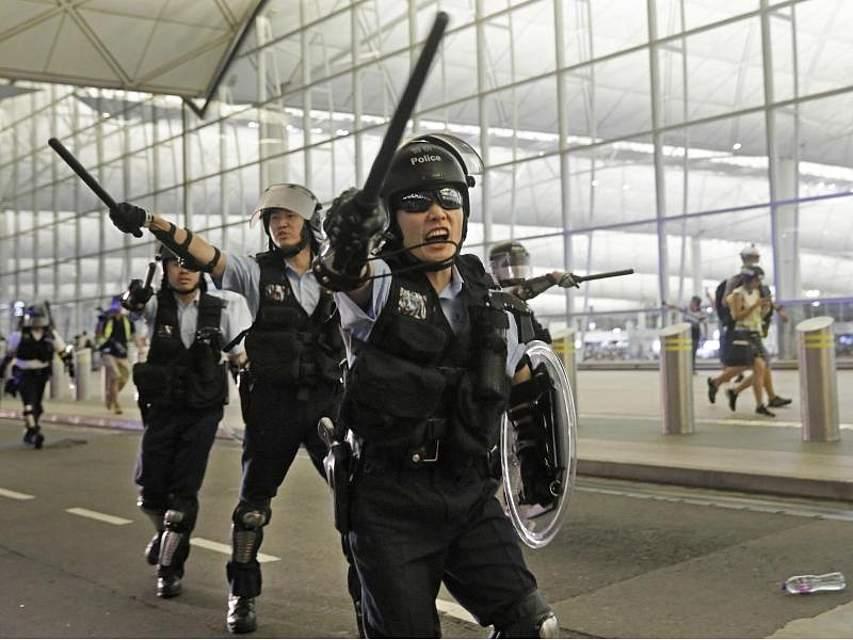 Polizisten mit Schlagstöcken im Hongkonger Flughafen an. Bei Protesten Tausender Regierungskritiker ist es zu gewaltsamen Zusammenstößen gekommen. Foto: Vincent Yu/AP
