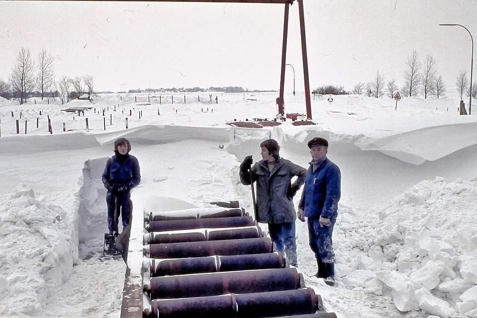"""Tief verschneit: Meister Tabel und Lehrjungs. Karsten Wessels aus Nordhastedt schreibt zu seinem Foto: """"Ich war in der Zeit als Schiffbauer auf der Büsumer Werft tätig. In Nordhastedt bauten wir unser Haus. Zum Jahreswechsel arbeiteten wir fieberhaft an der Fertigstellung, um bald einziehen zu können. Am Sylvester-Tag 1978 war ich mit Fliesenlegearbeiten im Bad beschäftigt. Die Heizung lief, und es war wohlig warm auf der Baustelle. Während draußen der Schneesturm zunahm, arbeitete ich zügig weiter. Gegen 17 Uhr schaute ich raus und stellte fest, dass ich besser nach Hause (Osterwohld) fahre. Ich schaffte es gerade noch durchzukommen. Der PKW hatte nur auf der getriebenen Vorderachse M&S Winterreifen. Der Stromausfall in der Neujahrsnacht wurde mit Ofenheizung und Kerzen gut gemeistert. Nach Neujahr gab es kein Durchkommen nach Büsum. Wir hätten auch nicht arbeiten können, zu hoch war die Werft von Schneeverwehungen bedeckt. Eine Woche haben ortsansässige Kollegen die wichtigsten Arbeitsbereiche freigeschaufelt. Für die übrige Belegschaft galt Kurzarbeit. Es klingt fast wie eine Ironie, dass wir zu der Zeit Kühlschiffe bauten. In ungeheizten Schiffbauhallen bei minus 10 Grad mit Stahl zu arbeiten ist schon eine Herausforderung. Aber wir haben uns warm gearbeitet."""""""