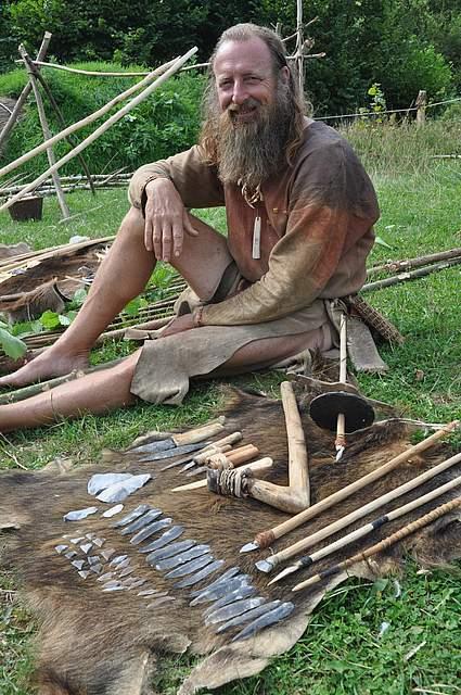 Werner Pfeifer neben verschiedenen steinzeitlichen Klingen, Messern, Pfeilen und Werkzeugen.