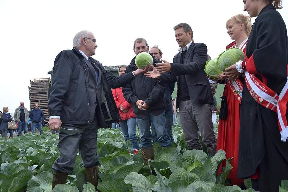 Kreispräsident Hans Harald Böttger verteilt erste Kohlkäpfe an die Kohlregentinnen und Landwirtschaftsminister Robert Habeck.