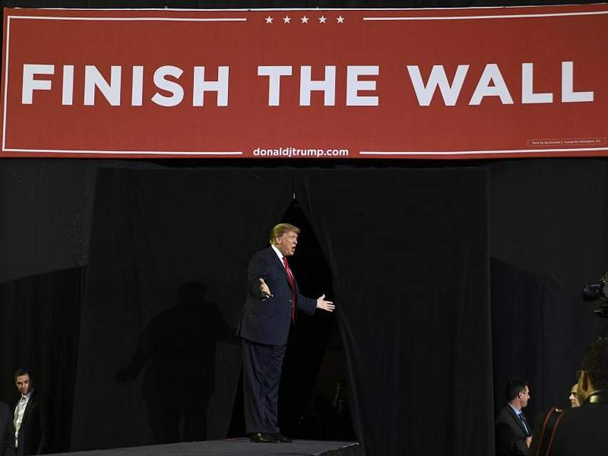 US-Präsident Donald Trump kommt zu einer Kundgebung vor Anhängern in El Paso im US-Bundesstaat Texas; hinter ihm hängt ein Banner mit derAufschrift «Finish The Wall» (Baut die Mauer fertig). Foto: Susan Walsh/AP