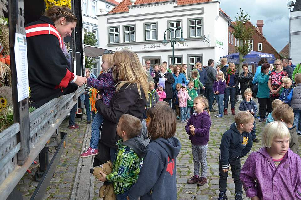Kohlregentin Maren I. verteilt Siegerurkunden an die Kinder der Kindergärten und Schulen, die beim Erntekronenbastelwettbewerb teilgenommen hatten.