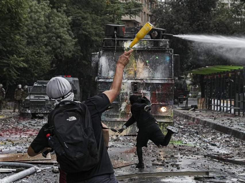 In Santiago de Chile attackieren Anti-Regierungs-Demonstranten einen Wasserwerfer der Polizei. Vorangegangen waren Proteste gegen soziale Ungleichheit und hohe Lebenshaltungskosten. Foto: Esteban Felix/AP/dpa