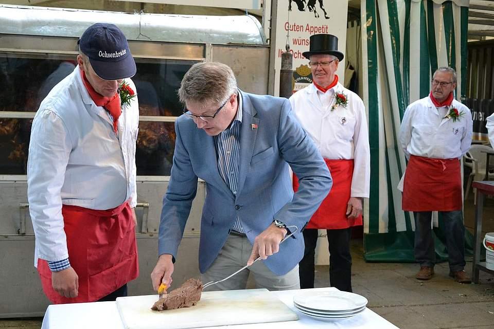 Landrat Stefan Mohrdieck schneidet den Pfingstochsen an.