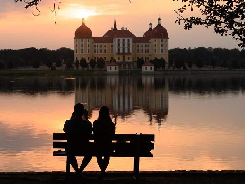 Wie gemalt sitzen zwei Passanten bei Sonnenuntergang vor dem Schloss Moritzburg in Sachsen auf einer Parkbank. Foto: Sebastian Kahnert/dpa-Zentralbild/dpa