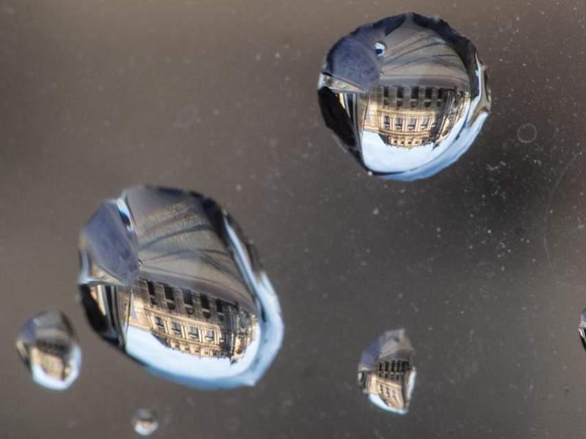 Die Dresdner Semperoper spiegelt sich in Regentropfen auf einem Autorückspiegel. Foto: Robert Michael/dpa-Zentralbild/dpa
