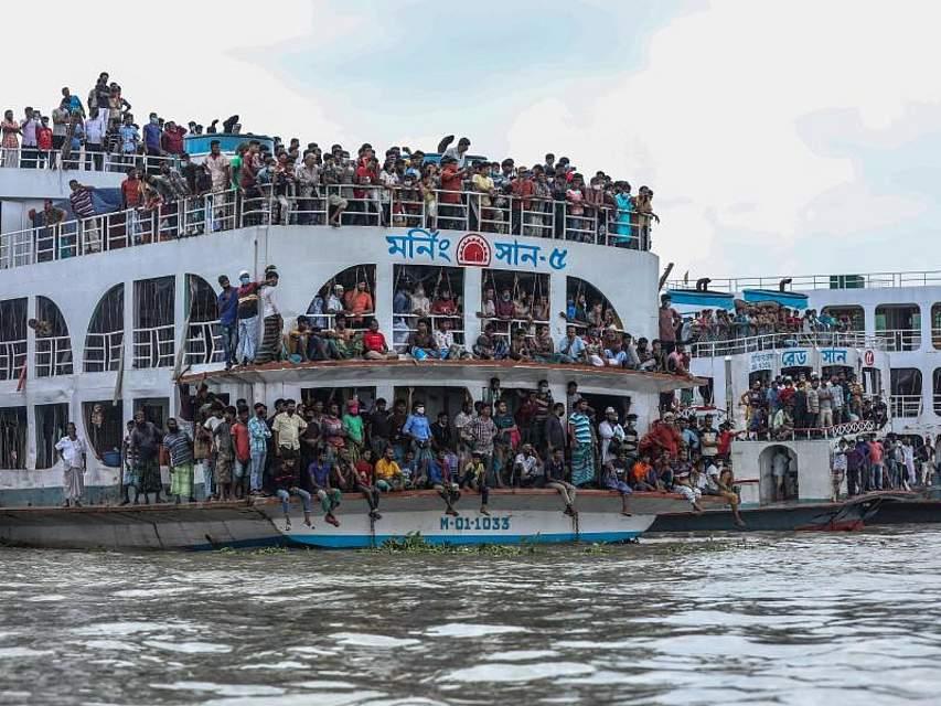 Dicht gedrängt stehen Menschen auf einem Boot in der Nähe von Dhaka und beobachten die Küstenwache bei ihrer Rettungsaktion nach einem Schiffsunglück. Bei dem Unglück in Bangladesch sind mindestens 32 Menschen gestorben. Foto: Md Manik/SOPA Images via ZUMA Wire/dpa