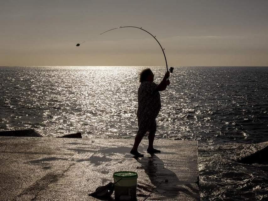 In Barcelona versucht eine Anglerin bei Sonnenaufgang ihr Glück. Foto: Emilio Morenatti/AP/dpa
