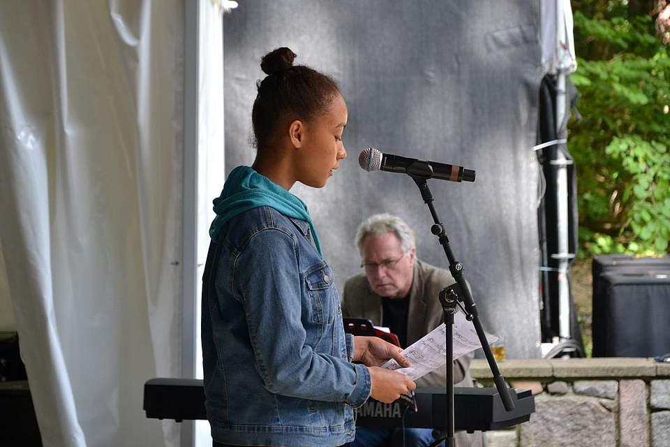 Rebecca Lohnert singt beim Waldgottesdienst, im Hintergrund am Piana Johannes Kirschbaum.