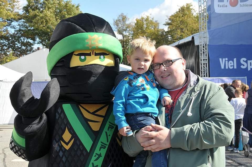 Auf den Armen seines Papas Patrick Weih aus Schmedeswurth traut sich der zweijährige Luca ganz dicht an den Lego-Ninjakämpfer. Foto: Voß