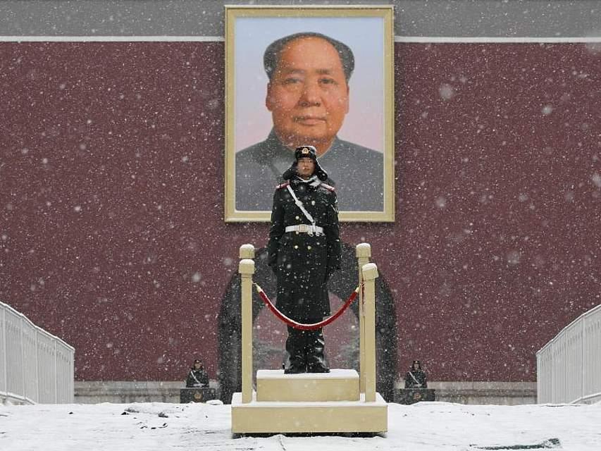 Ein Polizist steht unter einem Porträt von Mao Tsetung am Tor des Himmlischen Friedens in Peking. Foto:Andy Wong, AP