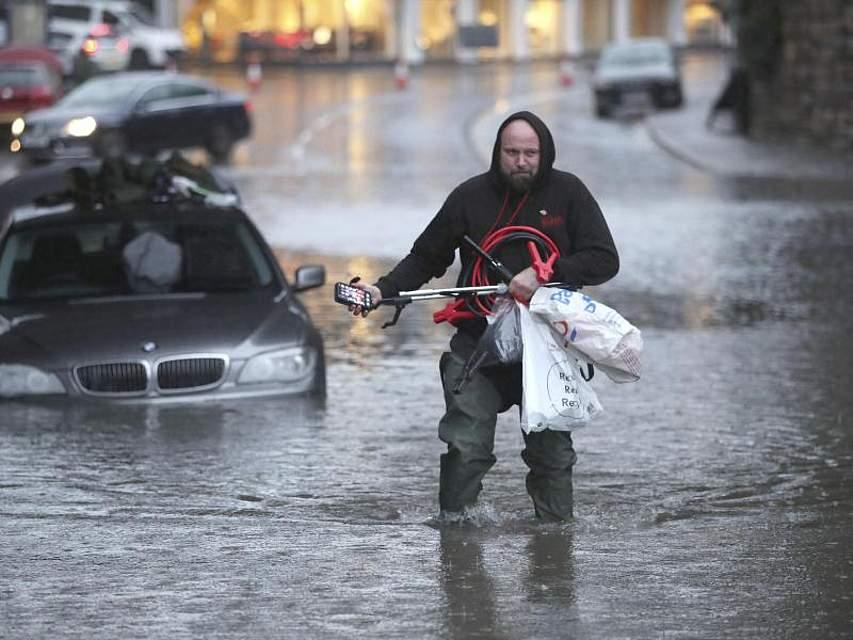 Ein Mann watet durch eine überflutete Straße in Sheffield, nachdem er Gegenstände aus seinem Auto gesammelt hat. Nach heftigen Regenfällen hat die britische Regierung mehr als 120 Flutwarnungen herausgegeben. Foto: Danny Lawson/PA/AP/dpa