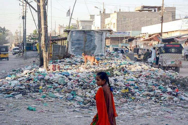 Auf einer Straße in der pakistanischen Hauptstadt Karachi passiert eine junge Frau einen großen Müllhaufen. Foto: Ppi/PPI via ZUMA Wire/dpa