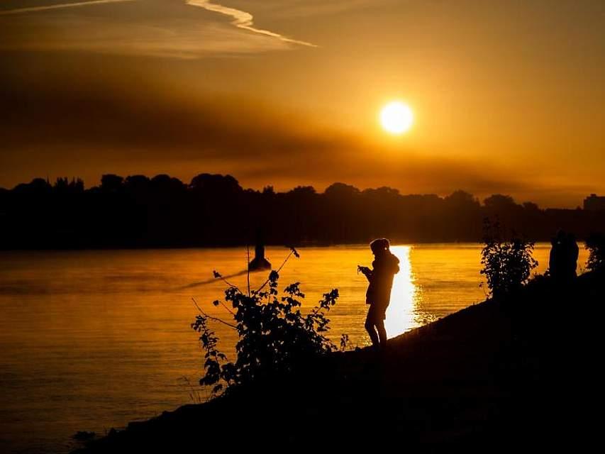Im Licht der aufgehenden Sonne wirkt die Weser unweit von Bremen wie einFluss aus Gold. Foto: Mohssen Assanimoghaddam