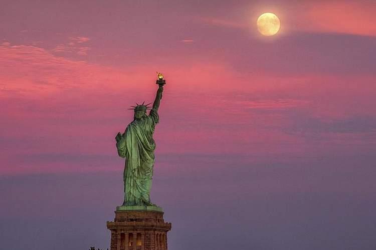 Über der Freiheitsstatue im New Yorker Hafen erhebt sich ein Vollmond. Foto: J. David Ake/AP