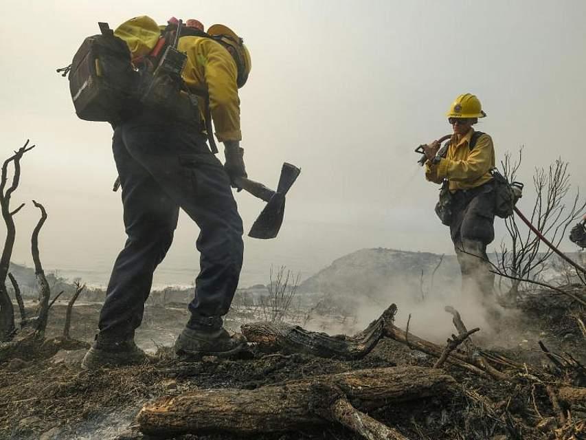 Feuerwehrleute des County of Santa Barbara Fire Departement löschen einen Brand am Straßenrand. Foto: Ringo H.W. Chiu/AP/dpa