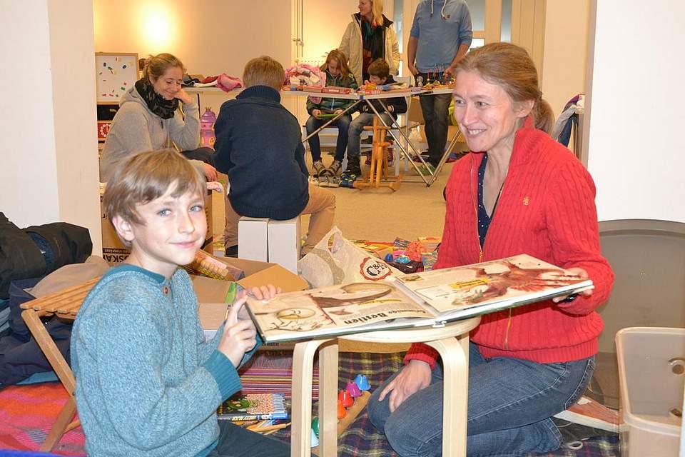 Flohmarkt der Grundschule: Thomas und seine Mutter Annette Burzin blättern in einem Bilderbuch, das zum Verkauf steht.