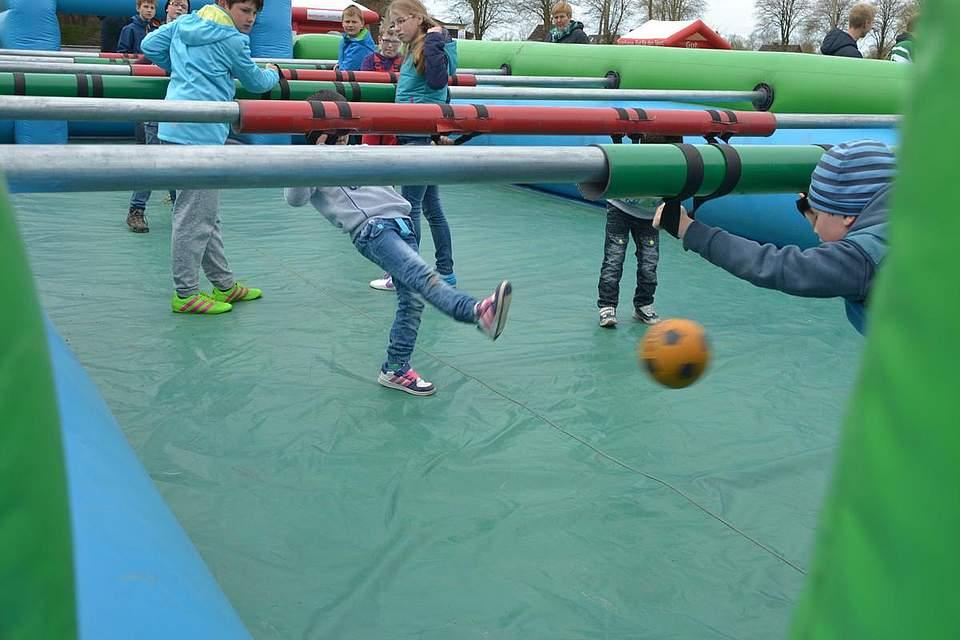 Kinder in Bewegung: Spaß beim Kickerspiel mit menschlichen Figuren.