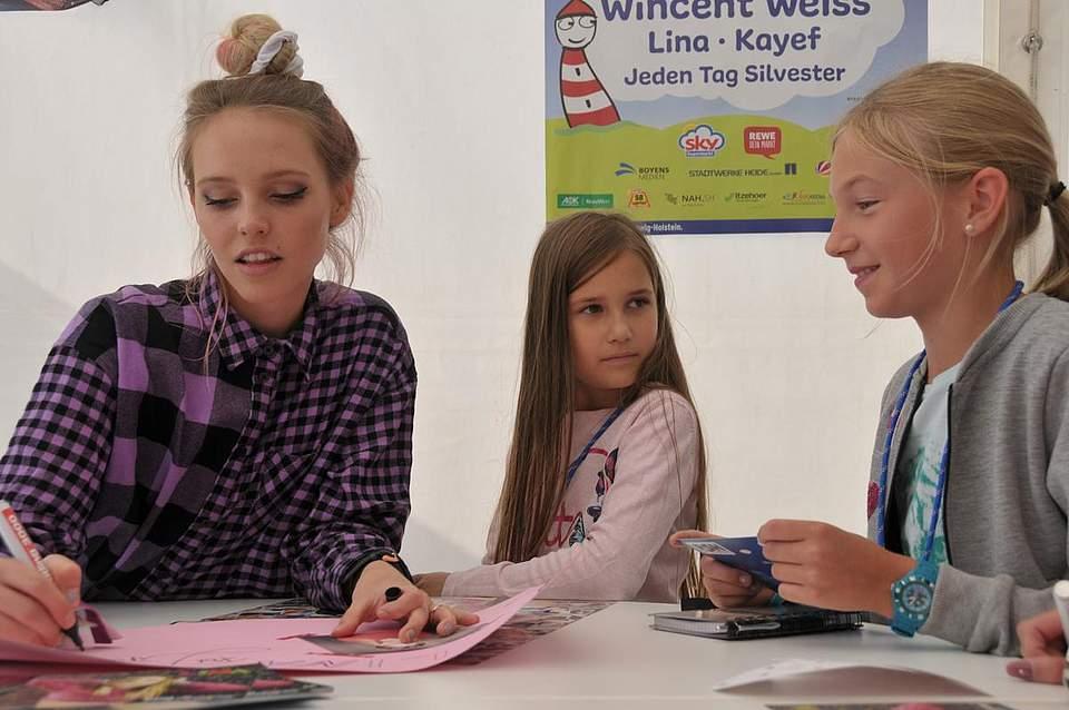 Lina signiert für ihre beiden Fans Ella Hülsmann (6) aus Kiel und Lina Schröder (9) aus St. Michel. Foto: Voß
