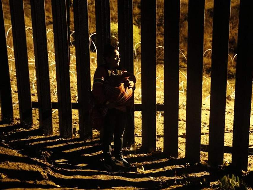 Eine Frau mit einem Baby im Arm blickt im mexikanischen Tijuana durch den US-Grenzzaun. Wegen der langen Wartezeit versuchen immer mehr Migranten, die Grenze zu den USA auf eigene Faust zu überqueren. Foto: Rebecca Blackwell/AP