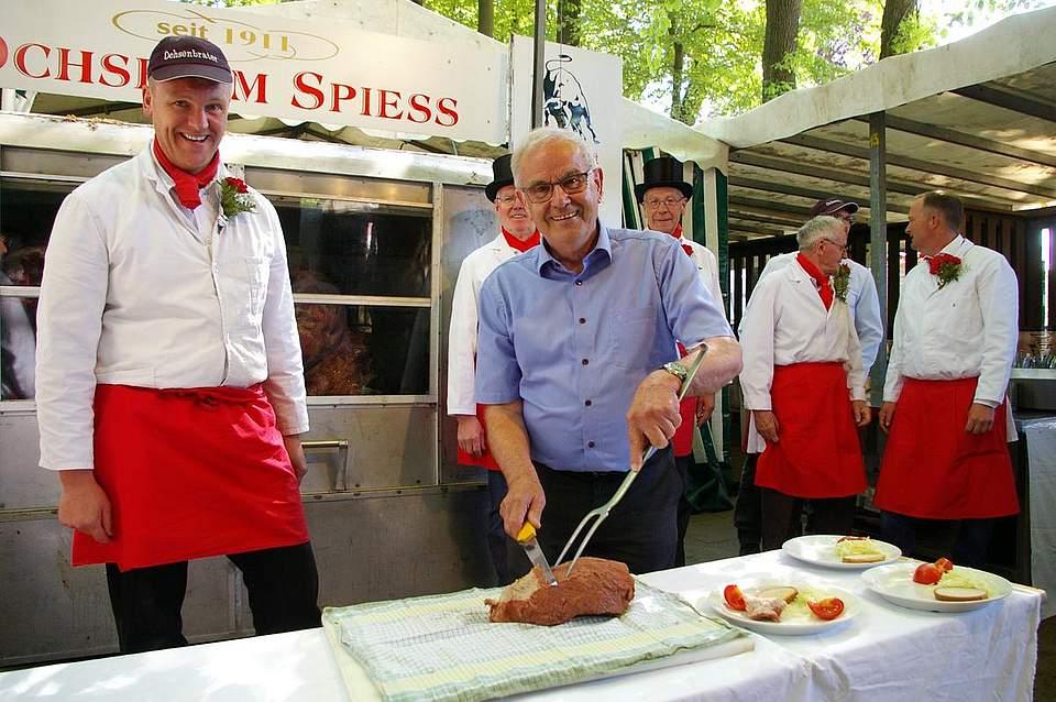 Der scheidende Kreispräsident Hans-Harald Böttger schneidet am Pfingstsonntag den Ochsen am Spieß an. Foto: Schatt