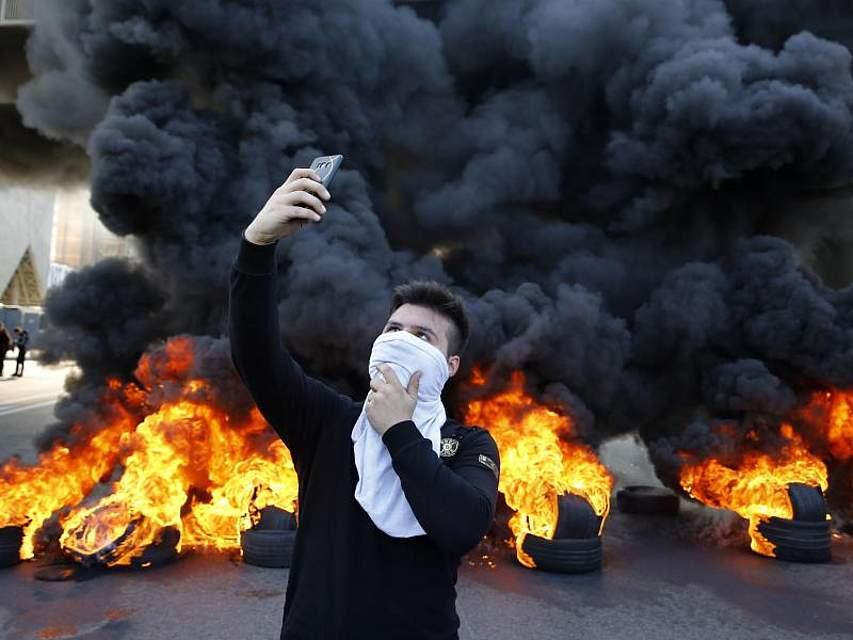 Ein regierungskritischer Demonstrant macht ein Selfie vor einer Barrikade aus brennenden Reifen, die eine Straße in Jal el Dib blockiert. Im Libanon wird seit Wochen gegen Misswirtschaft und Korruption protestiert. Foto: Bilal Hussein/AP/dpa