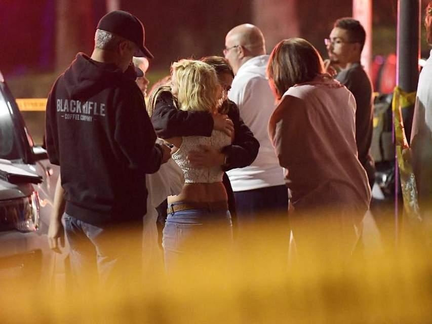 Menschen stehen außerhalb einer Bar in der kalifornischen Stadt Thousand Oaks und spenden sich Trost. Ein Mann hatte in dem Lokal um sich geschossen und zwölf Gäste erschossen. Foto: Mark J. Terrill/AP