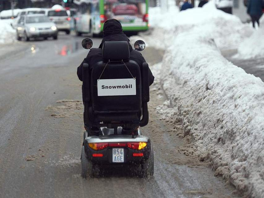 Ein Elektrorollstuhl fährt durch eine teilweise mit Schnee bedeckte Straße im winterlichen Garmisch-Partenkirchen. Foto: Angelika Warmuth