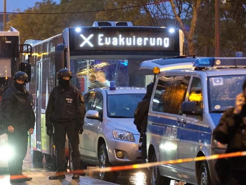 In Halle/Saale kam es zu Schüssen mit zwei Toten. Aufgrund der Gefahrenlage eskortiert die Polizei einen Bus mit der Aufschrift «Evakuierung». Foto: Sebastian Willnow/dpa-Zentralbild/dpa