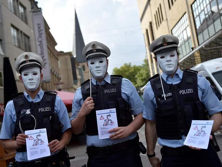Polizisten informieren in der Essener Innenstadt über Trickbetrüger, die sich als Polizisten ausgeben. Für der Aktion tragen sie weiße Masken. Foto: Caroline Seidel