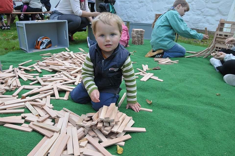 Carl-Jakob Blume (1) aus Brekendorf spielt bei den Heider Pfadfindern vergnügt mit den aufgearbeiteten Parkettstäben. Foto: Voß
