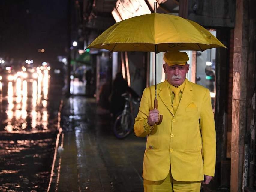 Abu Zakkour, in Aleppo bekannt als der «Gelbe Mann», geht mit einem Regenschirm durch die Straßen der syrischen Stadt. Der 68-Jährige kleidet sich seit 36 Jahren ausschließlich gelb, weil dies für ihn die Farbe der Liebe ist. Foto: Ammar Safarjalani/XinHua