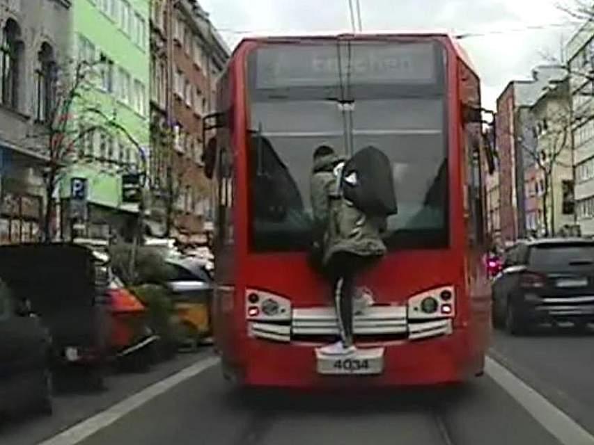 Das wird teuer: Das Videostandbild zeigt einen Mann, der in Köln auf der Kupplung einer Straßenbahn mitfährt, weil er nicht rechtzeitig eingestiegen war. Foto: Polizei Köln