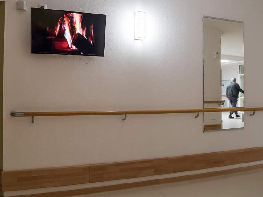 Kaminfeuer an der Wand: Ein Fernseher hängt im beschützenden Bereich für Alzheimer Patienten im Flur. Foto: Peter Kneffel