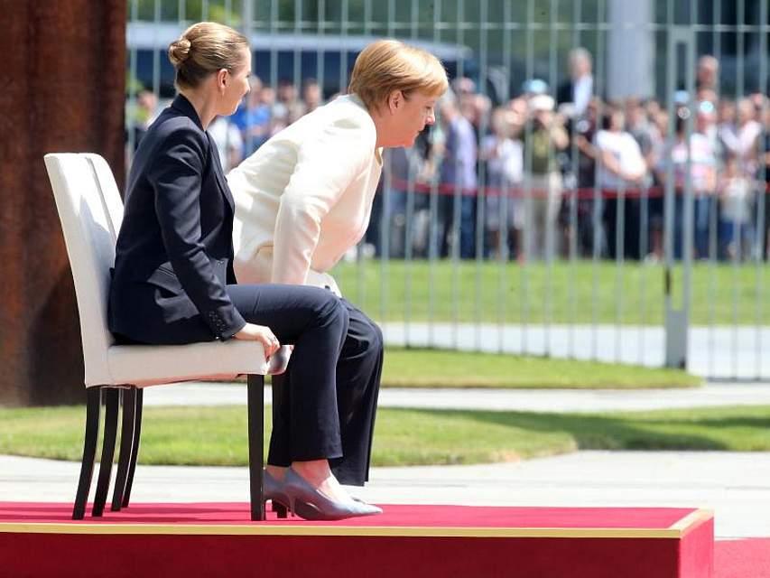 Kanzlerin Merkel und Dänemarks Ministerpräsidentin Frederiksen verfolgen das Abspielen der Hymnen im Kanzleramt. Nach Zitteranfällen bei der Begrüßung von Staatschefs hatte Merkel das Zeremoniell teilweise sitzend absolviert. Foto: Wolfgang Kumm