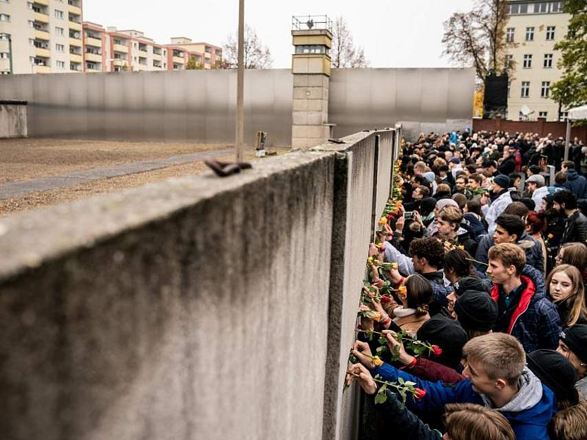 Bei einer Gedenkveranstaltung an der Bernauer Straße stecken Teilnehmer Blumen in Mauerschlitze. Mit bundesweiten Feierlichkeiten hat Deutschland an den Fall der Berliner Mauer am 9. November 1989 erinnert. Foto: Michael Kappeler/dpa