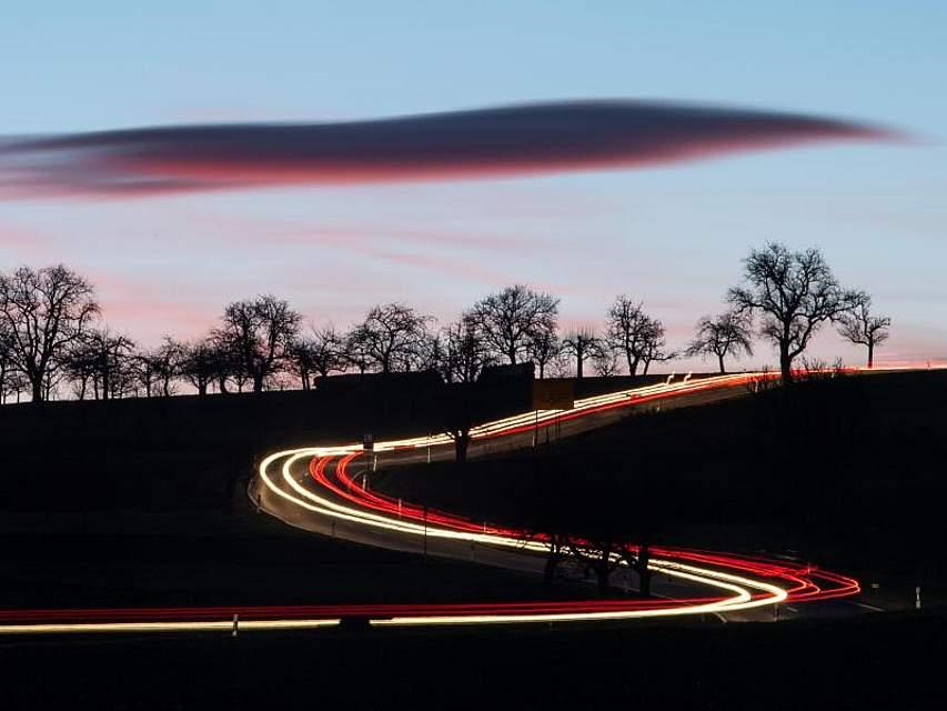 Autos fahren am frühen Morgen auf einer Landstraße nahe Vaihingen an der Enz; ihre Scheinwerfer hinterlassen eine Leuchtspur. Foto: Sebastian Gollnow/dpa