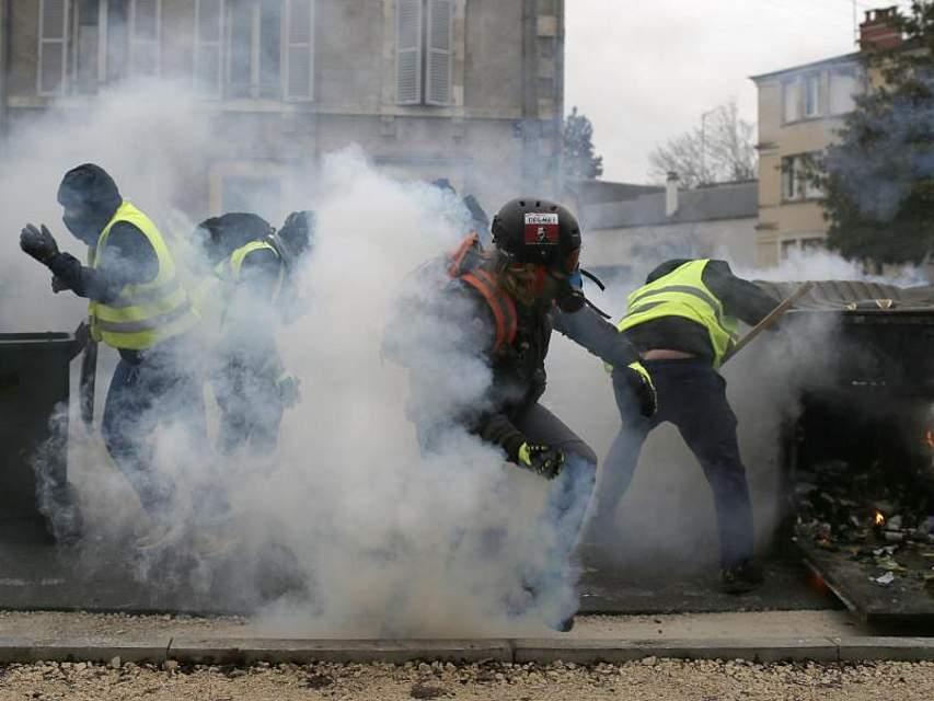 Teilnehmer einer Demonstration der «Gelbwesten» gehen in Bourges hinter ihren Barrikaden in Deckung, als Polizisten Tränengas einsetzen. In mehreren französischen Städten gab es den neunten Protest-Samstag in Folge. Foto: Rafael Yaghobzadeh/AP