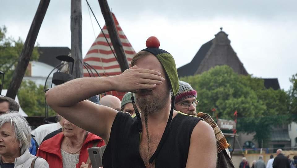 Diesem Gaukler soll der Apfel vom Kopf geschossen werden - da hält er sich lieber die Augen zu. Foto: Höfer