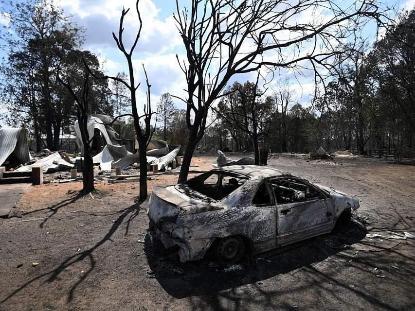 Ein abgebranntes Haus und ein ausgebranntes Auto stehen in dem Ort Rappville im Bundesstaat New South Wales. Buschbrände haben im Osten Australiens Dutzende Wohnhäuser und andere Gebäude zerstört. Foto: Dan Peled/AAP/dpa
