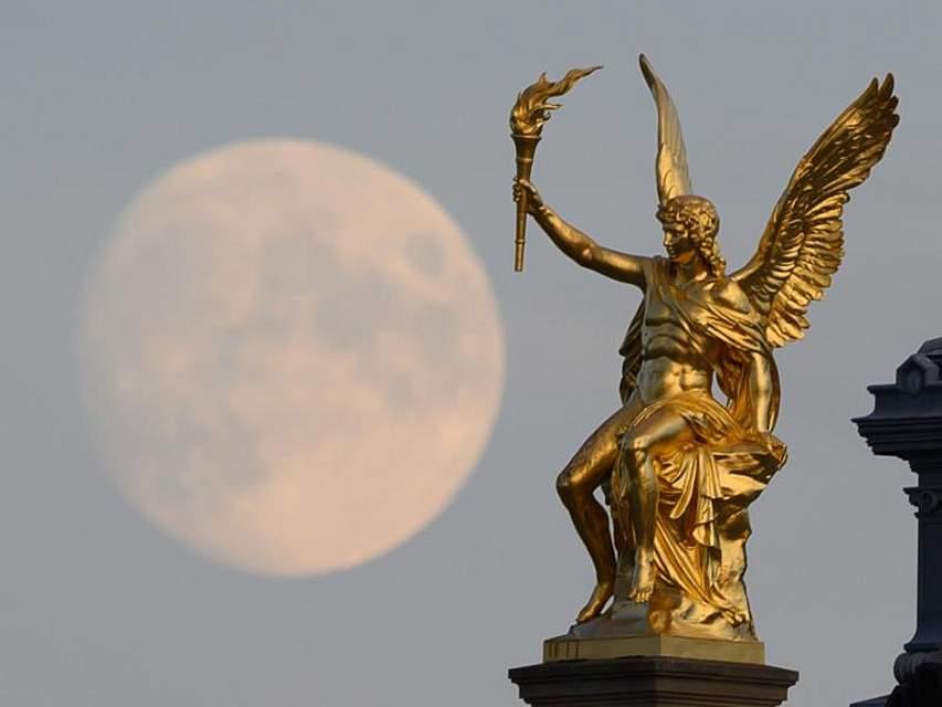 Der Mond geht hinter der vergoldeten Engelsfigur auf dem Dach der Hochschule für Bildende Künste inDresden auf. Foto: Sebastian Kahnert/dpa-Zentralbild/dpa
