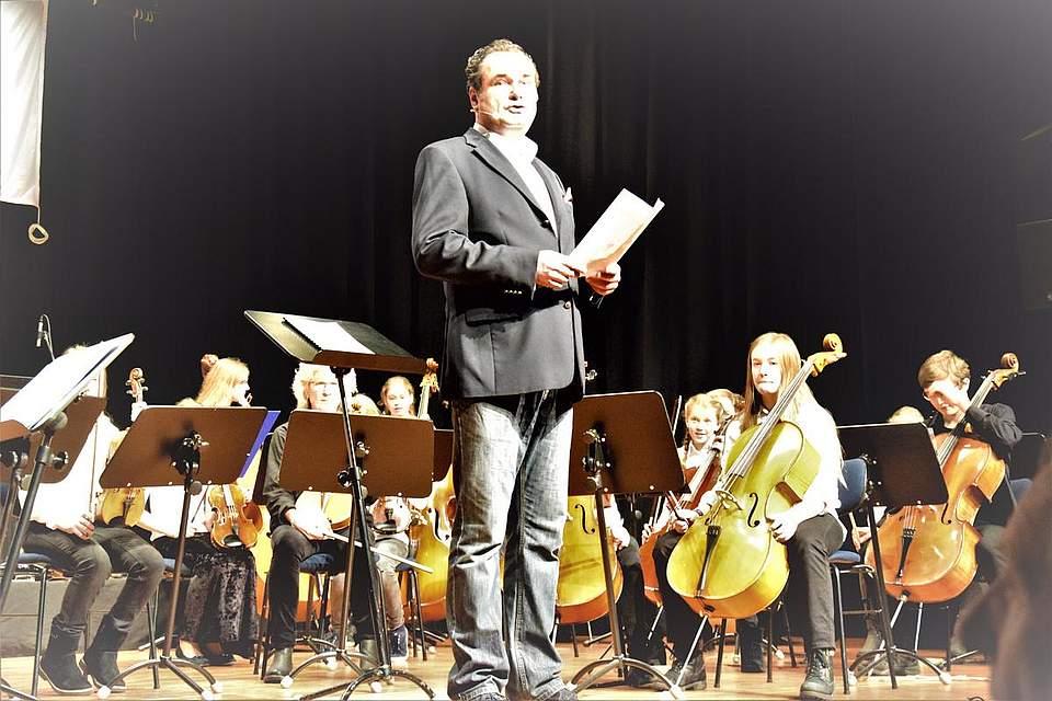 Moderator Stefan Schmid vor dem Dithmarscher Musikschulorchester DIMO.