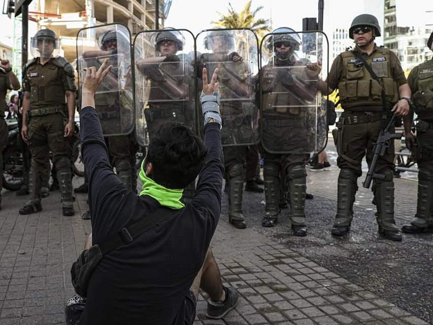 Bei Anti-Regierungs-Protesten in Santiago sitzt ein Demonstrant vor Polizisten. Seit Wochen demonstrieren in Chile zahlreiche Menschen gegen hohe Lebenshaltungskosten und soziale Ungleichheit. Foto: Esteban Felix/AP/dpa