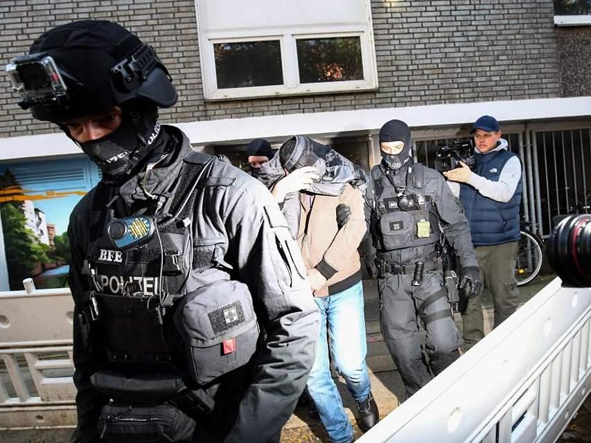 Ein Mann wird von Polizisten in Hamburg aus einem Haus geführt. Ermittler haben in mehreren Bundesländern Gebäude durchsucht. Der Verdacht der Terrorfinanzierung steht im Raum. Foto: Christian Charisius