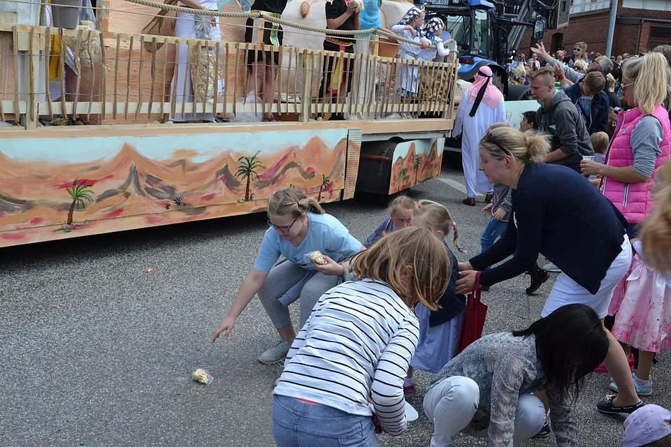 Kinder sammeln Bonbons auf.