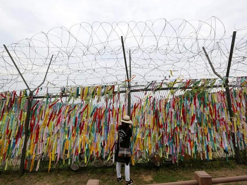 An der Grenze zu Nordkorea hängt eine Südkoreanerin ein Band mit dem Wunsch nach Frieden und Wiedervereinigung an einen Drahtzaun. Seoul und Pjöngjang befinden sich derzeit in einer Phase der Annäherung. Foto: Ahn Young-Joon/AP