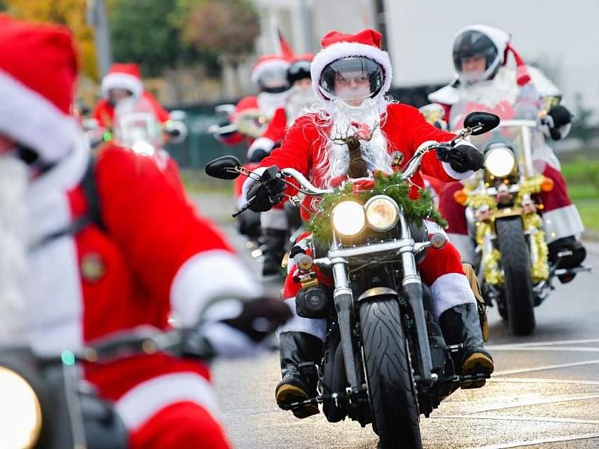 Diese Weihnachtsmänner kommen am Nikolaustag auf ganz besonderen Gefährten: Unter dem Motto «Harley Davidson riding Santas» rufen die Motorradfahrer in Lustadt (Rheinland-Pfalz) zur Unterstützung eines Heims für krebskranke Kinder auf. Foto: Uwe Anspach